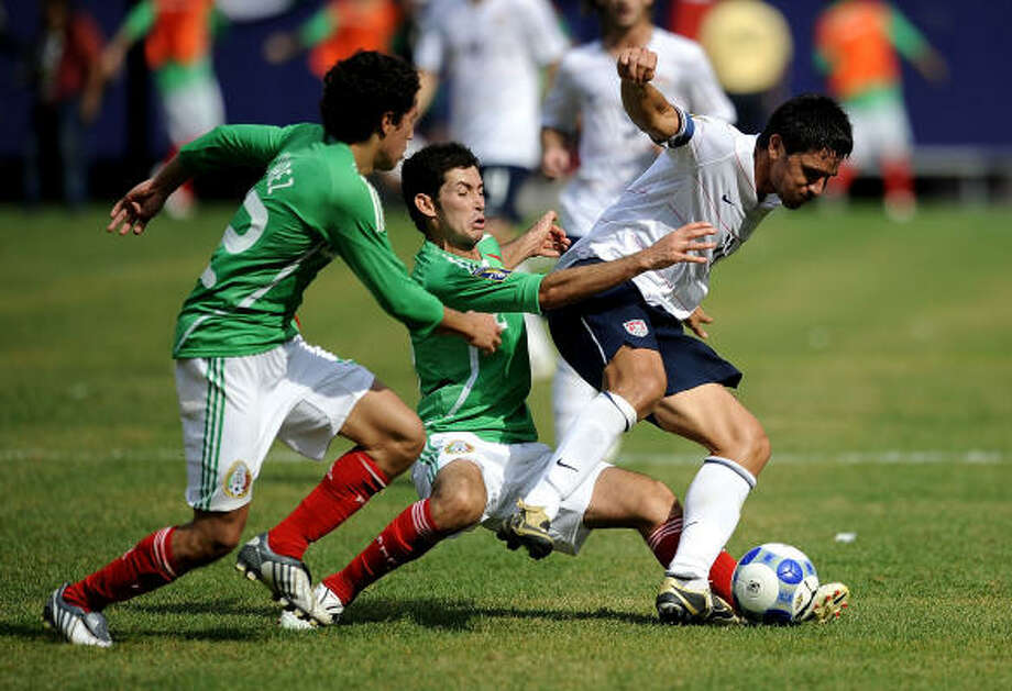 Efrain Juarez (22) and Israel Castro (8) of Mexico fight for the ball with Brian Ching (11) of the United States. Photo: Jeff Zelevansky, Getty Images