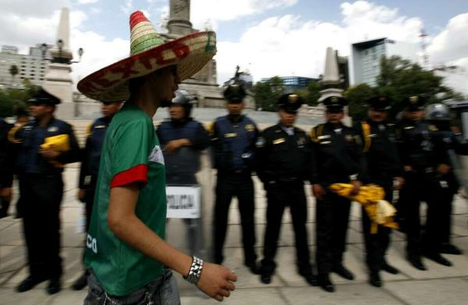 A Mexican soccer fan celebrates his team's victory in front of a line of police at the Angel of Independence monument in Mexico City. Photo: Marco Ugarte, AP