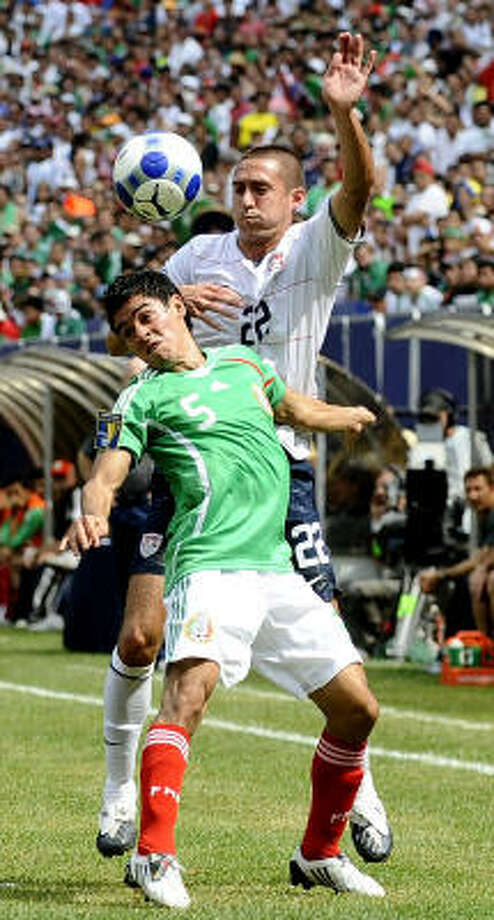 Fausto Pinto of Mexico, front, and Davy Arnaud of the United States fight for the ball in the CONCACAF Gold Cup championship match. Photo: Jeff Zelevansky, Getty Images