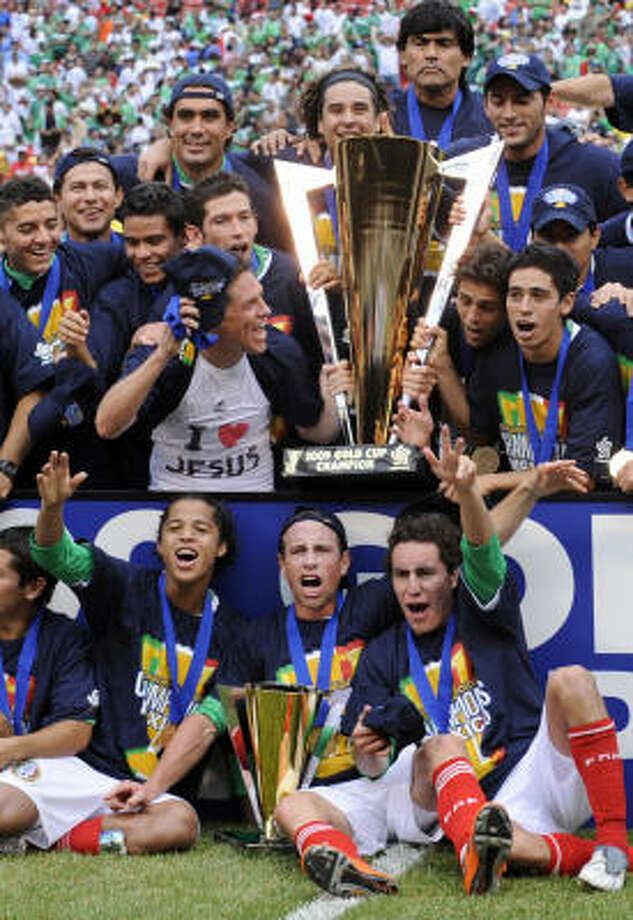 Mexico's Giovani Dos Santos, front left, Garardo Torrado, front center, Efrain Juarez, front right, and their teammates celebrate with the trophy after defeating the United States 5- 0 in the CONCACAF Gold Cup soccer final. Photo: Bill Kostroun, AP