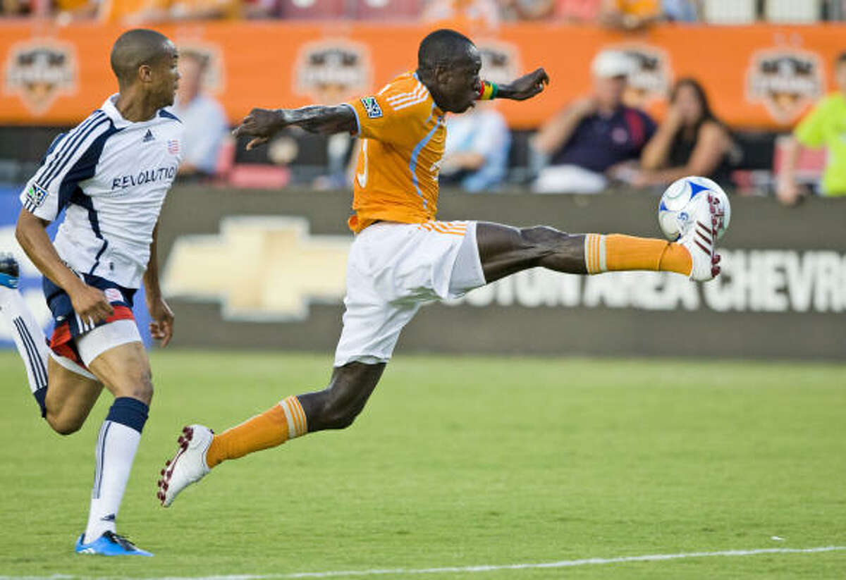The Dynamo's Dominic Oduro stretches to control the ball behind New England's Darrius Barnes, left.