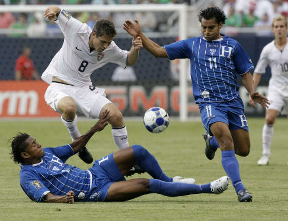 United States' Logan Pause, center, fights for the ball with Honduras' Mariano Acevedo, right, and Marvin Chavez during the first half. Photo: Charles Rex Arbogast, AP