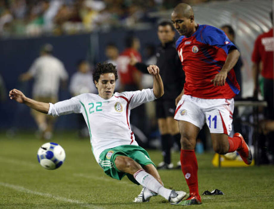 Mexico's Efrain Juarez, left, tackles Costa Rica's Andy Herron during the second half. Photo: Nam Y. Huh, AP