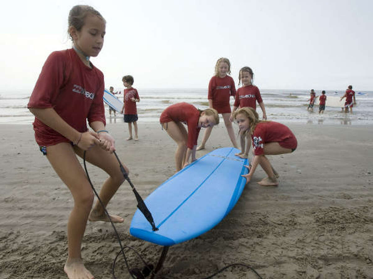 Isabella Garofalo of Houston who turns ten-years old on July 1st picks up a surf board with her group during the Bilabong / Ohana Surf and Skate Shop surf camp in Galveston.