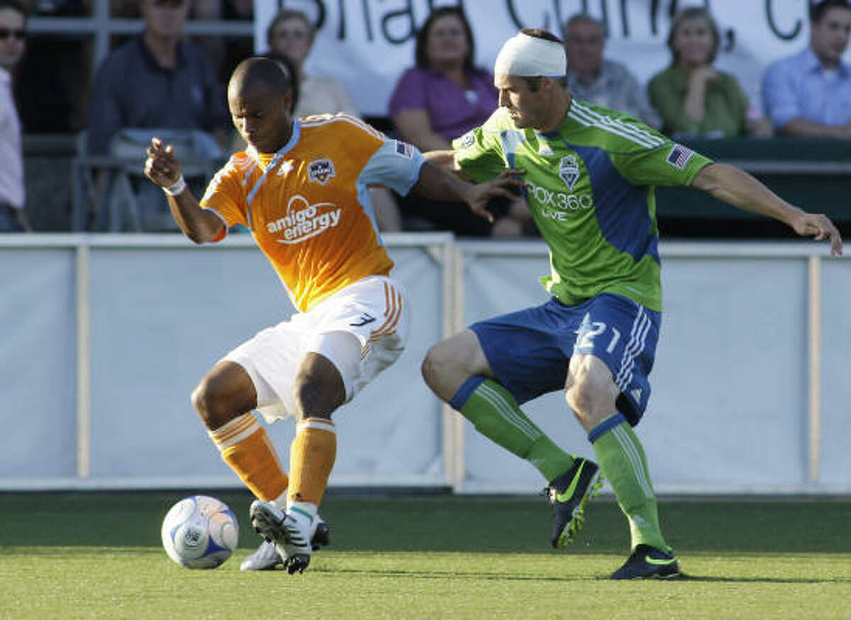 With his head bandaged from an injury earlier in the game, Seattle Sounders' Nate Jaqua, right, battles for the ball with Houston Dynamo's Julius James in the first half.
