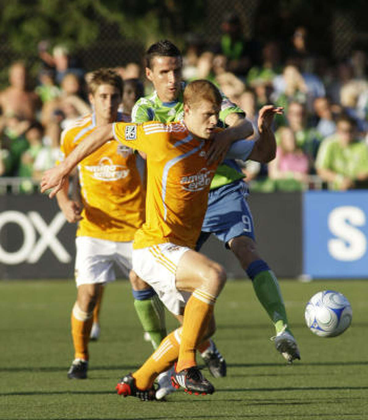 Houston Dynamo's Andrew Hainault, front, battles Seattle Sounders' Sebastien Le Toux for the ball in the first half.