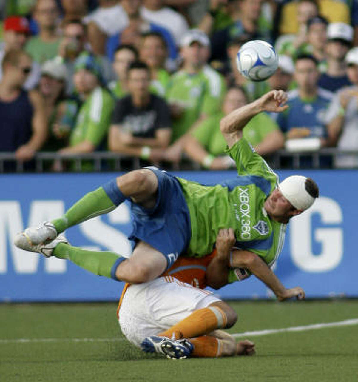 Seattle Sounders' Nate Jaqua comes down on top of Houston Dynamo's Mike Chabala in the second half.