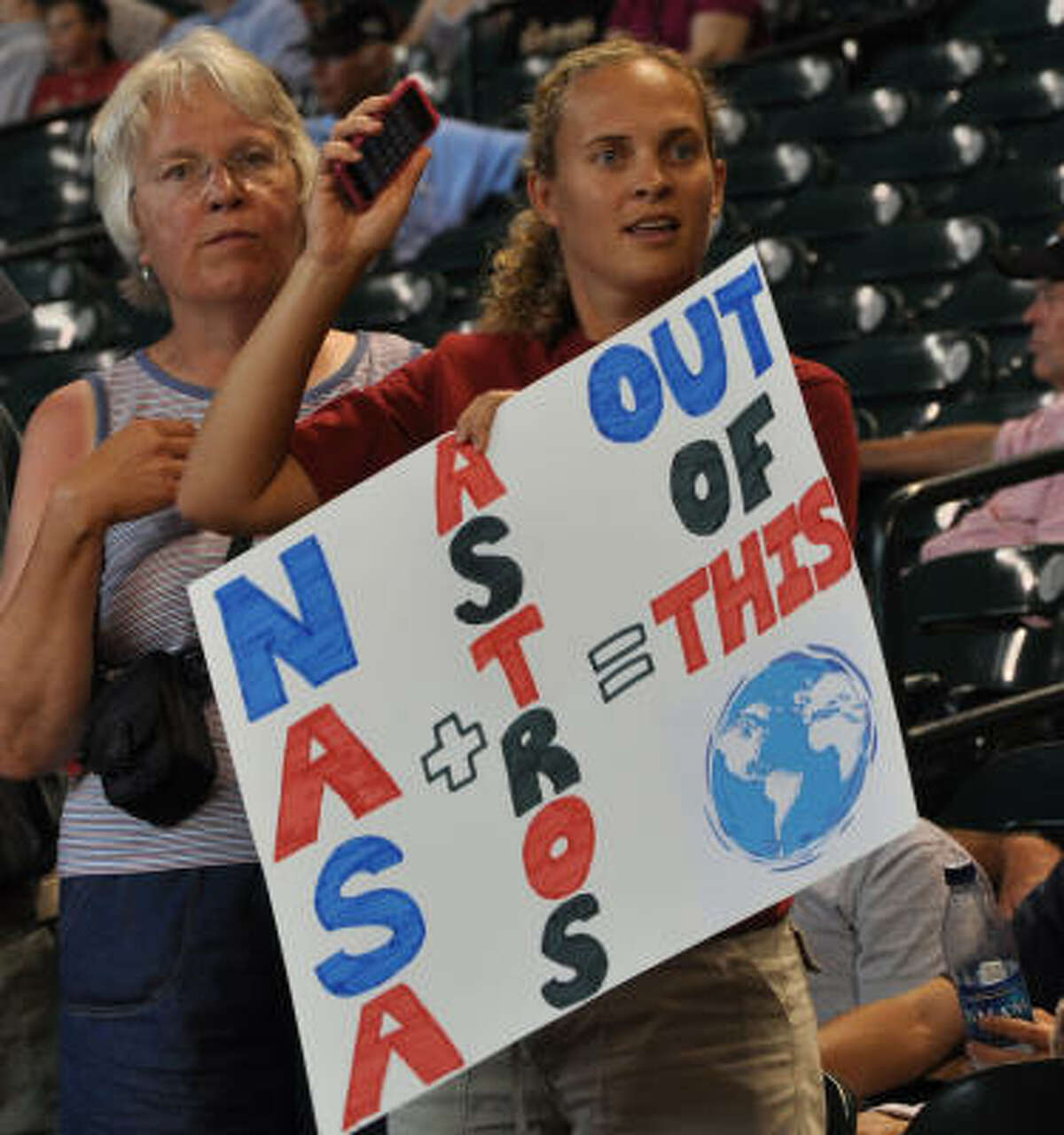Neva Metcalf holds a sign for her astronaut sister, singing the national anthem.
