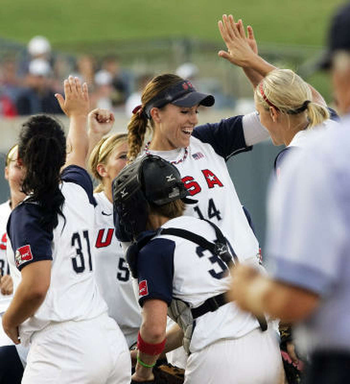 Starting pitcher Monica Abbott (14) celebrates with teammates after striking out the side in the first inning.