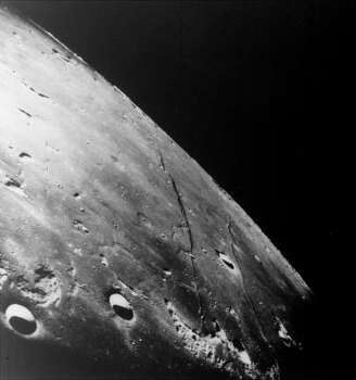 This oblique photograph of the moon looks generally northwest into the Sea of Tranquility, projected landing site for the Apollo 11 astronauts.  The lower (nearest) linear feature is the Cauchy Scarp.  The upper linear feature is the Cauchy Rille.  The prominent crater Cauchy lies between the rille and the scarp.  This picture was made from the Apollo 8 spacecraft late December, 1968. Photo: NASA, Associated Press