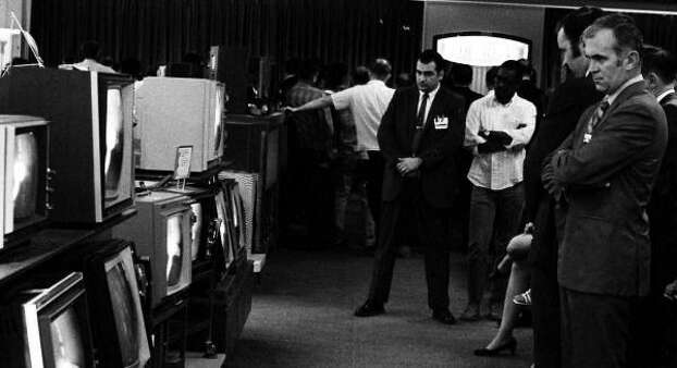 A group of unidentified people gather around televisions in a Sears Dept. store in White Plains, N.Y. to watch the lift off of Apollo 11 on July 16, 1969. Photo: ASSOCIATED PRESS