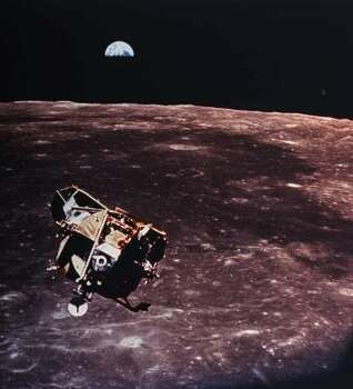 The Apollo 11 Lunar Module ascent stage can be seen from the command service module during rendezvous in lunar orbit July 20, 1969. The large, dark-colored area in the background is Smith's Sea, centered at 85 degrees east longitude and 2 degrees south latitude on the lunar near side, looking west as the Earth rises above the Lunar horizon.  It was announced Thursday, March 5, 1998, that small, scattered pockets of ice have been found beneath the lunar surface by a robot survey spacecraft that has spent the last month mapping the moon. Photo: AP
