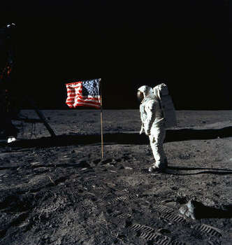 This NASA handout photo taken on July 20, 1969 shows Astronaut Edwin E. Aldrin, Jr., lunar module pilot of the first lunar landing mission, posing beside the deployed United States flag during Apollo 11 Extravehicular Activity (EVA) on the lunar surface area called the Sea of Tranquility. With one small step off a ladder, Neil Armstrong, commander of the Apollo 11 mission, became the first human to set foot on the moon on July 20, 1969, before the eyes of hundreds of millions of awed television viewers worldwide. With that step, he placed mankind's first footprint on an extraterrestrial world and gained instant hero status. The Lunar Module (LM) is on the left, and the footprints of the astronauts are clearly visible in the soil of the Moon. Photo: HO, AFP/Getty Images