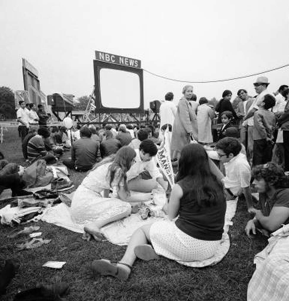 Click through to see photos of people watching the 1969  Apollo 11 moon mission. A crowd gathers to watch the Apollo 11 crew land on the moon, July 20, 1969, Central Park, New York.