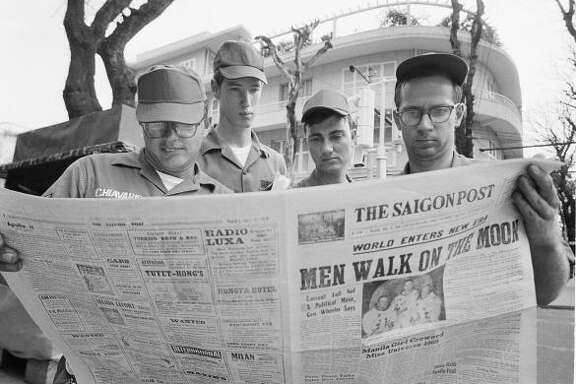 American servicemen pause on a downtown Saigon Street to read a local newspaper account of the Apollo 11 lunar landing, July 21, 1969, Ho Chi Minh City, Vietnam. From left are Air Force. Sgt. Michael Chivaris, Clinton, Mass., Army Spec. 4 Andrew Hutchins, Middlebury, Vt.; Air Force Sgt. John Whalin, Indianapolis, Ind.; and Army Spec. 4 Lloyd Newton, Roseburg, Ore.