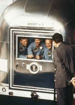 "In this July 24, 1969 file photo, President  Richard Nixon, back to camera, greets the Apollo 11 astronauts in the quarantine van on board the U.S.S. Hornet after splashdown and recovery.   The Apollo 11 crew from left:  Neil Armstrong, Michael Collins, and Edwin ""Buzz"" Aldrin. Photo: AP"