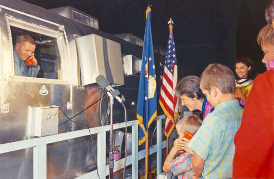 Neil A. Armstrong, commander of the Apollo 11 flight, greets his son Mark on telephone intercom system, while his wife Jan and another son Eric look on. Armstrong had just arrived in early morning with the Mobile Quarantine Facility at Ellington Air Force Base. Armstrong and fellow astronauts will remain in the MQF until arrival and confinement in the Crew Reception Area of the Lunar Receiving Laboratory at the Manned Spacecraft Center. Quarantine period will end on August 10, 1969.