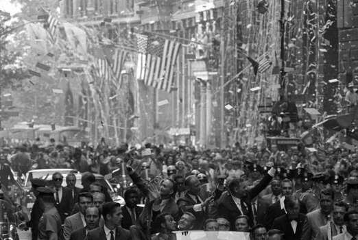 In this Aug. 13, 1969 file photo,  amid ticker tape and American flags, Apollo 11 astronauts wave to welcoming New Yorkers during parade up lower Broadway on Wednesday, in New York. The spacemen, from left, are Michael Collins, Edwin Aldrin, Jr., and Neil A. Armstrong. Photo: Eddie Adams, AP