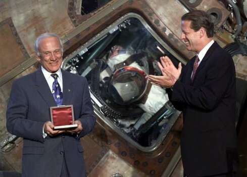 "Apollo 11 astronaut Edwin A. ""Buzz"" Aldrin is applauded by Vice President Al Gore after Gore presented him the Langley Gold Medal for aviation Tuesday, July 20, 1999 at a ceremony in the Smithsonian Air and Space Museum in Washington. The event marks the 30th anniversay of the first landing on the moon by the three Apollo 11 crew members. In the background is the original Apollo 11 capsule. Photo: DOUG MILLS, ASSOCIATED PRESS"