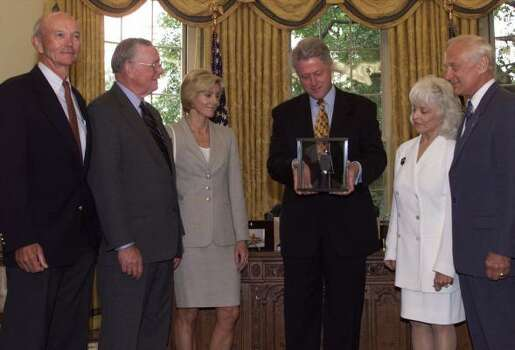 "President Clinton looks at a piece of moon rock presented to him by Apollo 11 crew members Michael Collins, left, Neil Armstrong, second left, and Edwin A. ""Buzz"" Aldrin, right, during a visit to the White House. Carol Armstrong, wife of Neil, third left, and Lois Aldrin, second right, wife of Buzz, joined the presentation. Tuesday marks 30th anniversary of the first landing on the moon, and the men of Apollo 11 received the prestigious Langley Gold Medal for aviation Tuesday, as well as, met with Clinton. Photo: RON EDMONDS, ASSOCIATED PRESS"