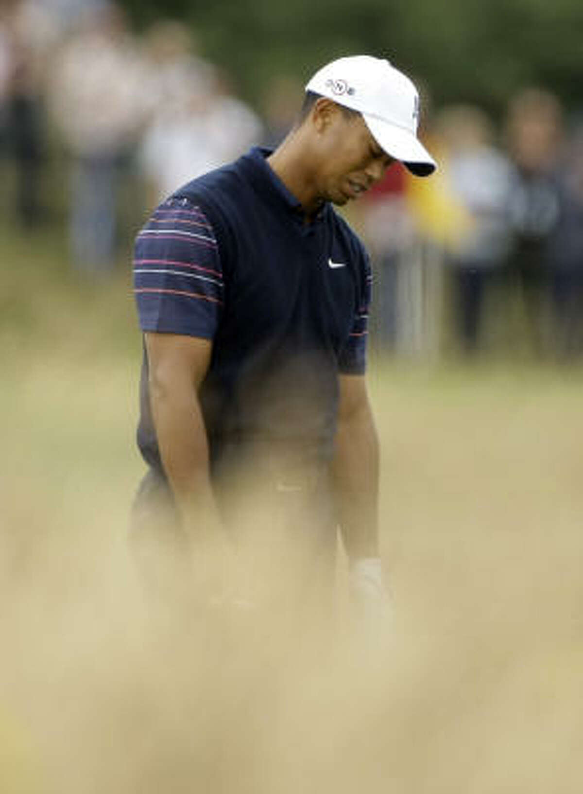 Tiger Woods reacts after playing out of the rough on the 13th hole during the first round. He recovered for par.