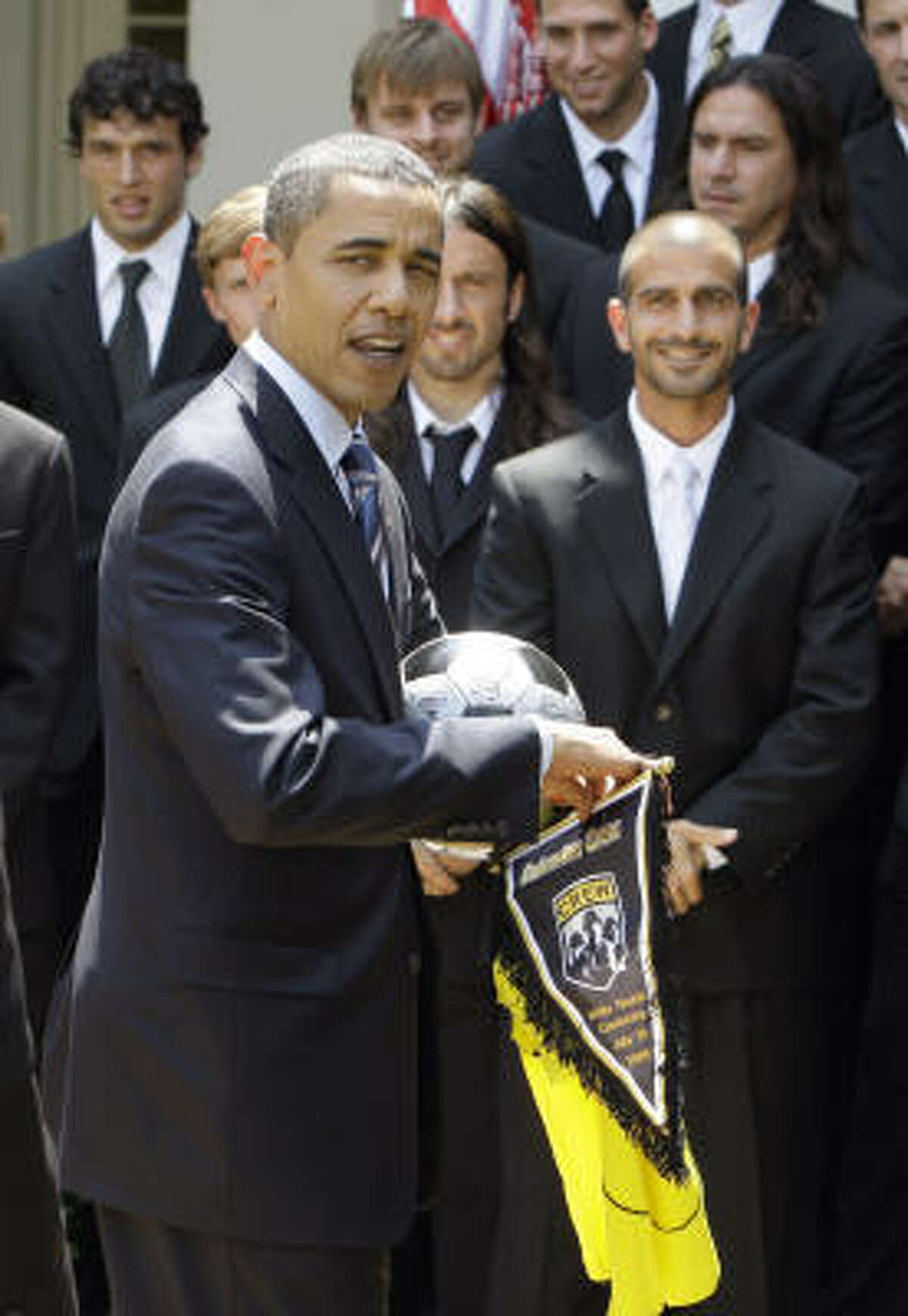 President Barack Obama collects a jersey, a ball and a pennant from the Crew.