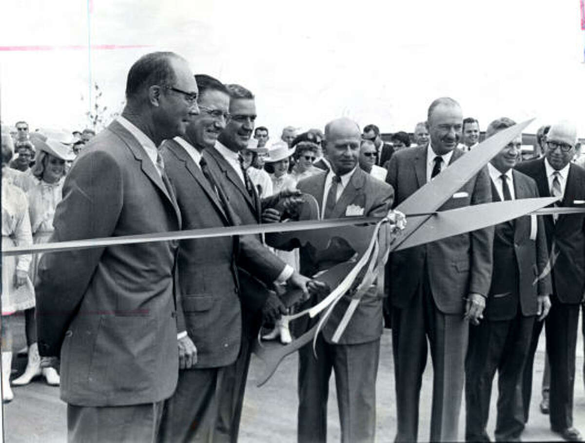 """Clear Lake in the Apollo era The suburban Clear Lake area grew along with NASA's Manned Aircraft Center, later to be called Johnson Space Center. In this 1963 photo, Texas Gov. John Connally uses giant scissors to snip the ribbon on a new development project called Clear Lake City. Two years later, a Clear Lake City brochure boasted that 5,500 people were employed at the space center and pointed out that """"employees are happier working in pleasant surroundings than on industrial row."""" Today nearly 17,000 people work for NASA or one of its contractors."""