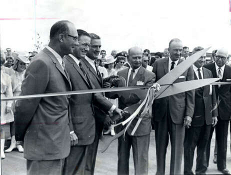"The suburban Clear Lake area grew along with NASA's Manned Aircraft Center, later to be called Johnson Space Center. In this 1963 photo, Texas Gov. John Connally uses giant scissors to  snip the ribbon on a new development project called Clear Lake City. Two years later, a Clear Lake City brochure boasted that 5,500 people were employed at the space center and pointed out that ""employees are happier working in pleasant surroundings than on industrial row."" Today nearly 17,000 people work for NASA or one of its contractors. Photo: Chronicle"