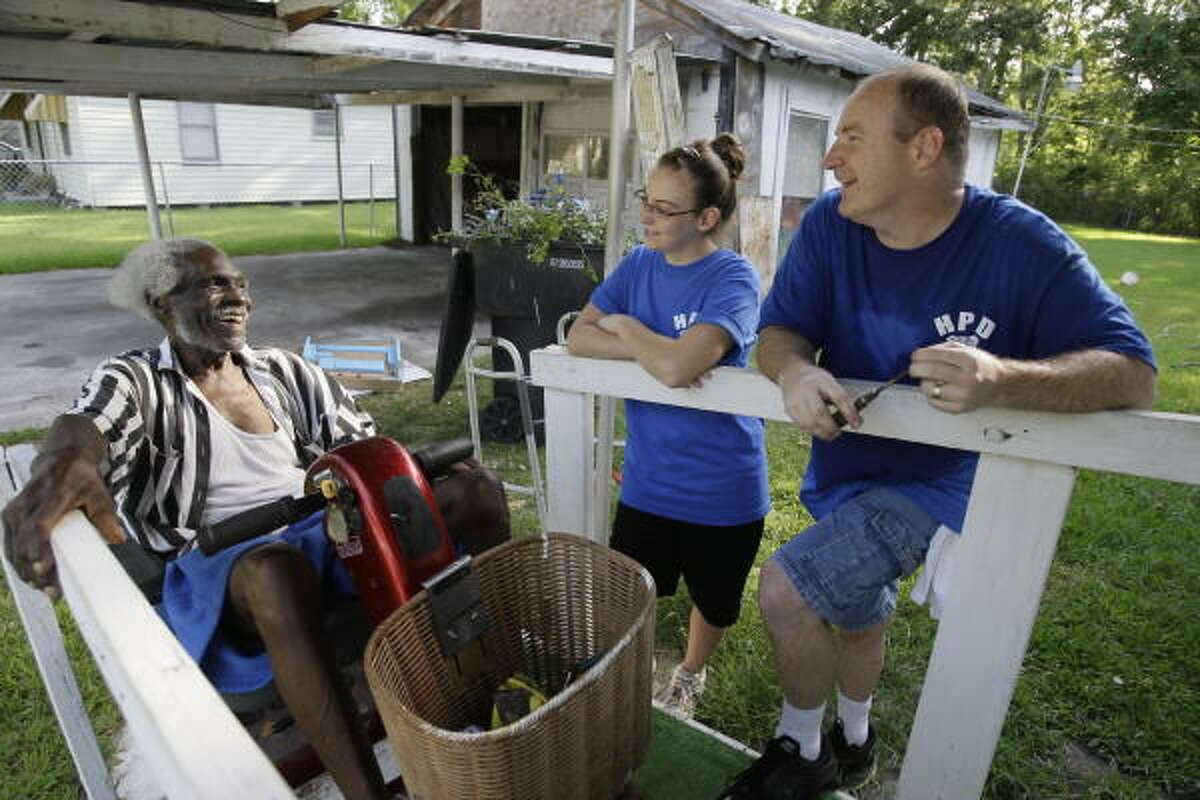 Woodrow Ward, 91, shares a laugh with Houston Police Sgt. Jim Babb and his daughter, Brittaney Babb, 13, as the HPD's Blue Crew along with Lowe's of Tomball and Pittsburgh Paint help with improvements to the home of Woodrow and his wife 84-old-year wife, Mavis, on Green Meadow Lane in Acres Homes. A wheelchair ramp and front porch were built last week. Hurricane Ike had uprooted two large trees in their yard that damaged the porch making it unusable. Today the house was painted and landscaping added.