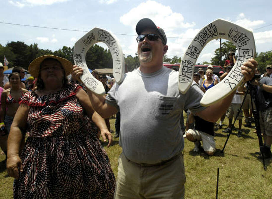 """Redneck Horseshoe"" winner Ryan ""Iceberg"" Berg of Flovilla, Georgia, celebrates with the crowd his winning throw during the 13th Annual games July 11, 2009 in East Dublin, Georgia. Started in 1996 as a spoof for the summer Olympics held in Atlanta, the games feature bobbing for pigs feet, hub cap hurling and the mud pit belly flop contest for trophies. Photo: Stephen Morton, Getty Images"