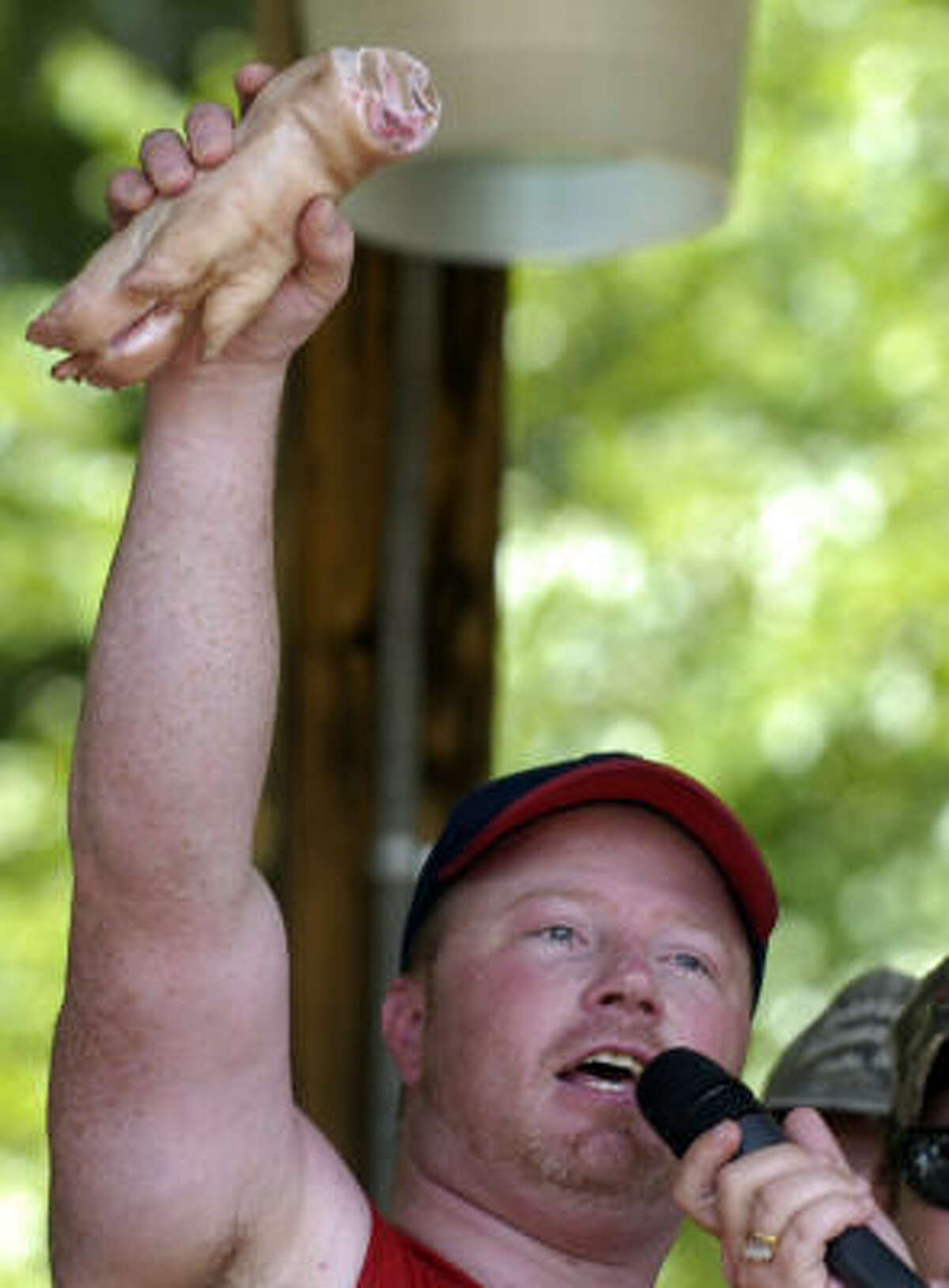 Bobbing for Pigs Feet winner Eric Outler holds a raw pig foot over his head after winning the event.