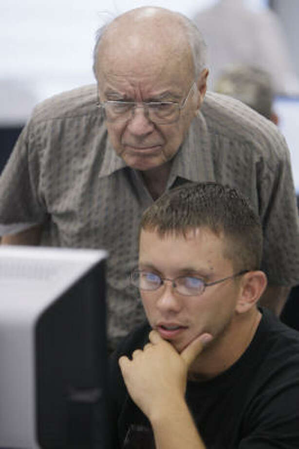 Wayne Hemingway assists Micha Hagan of Cypress at a computer during class. Photo: Melissa Phillip, Chronicle