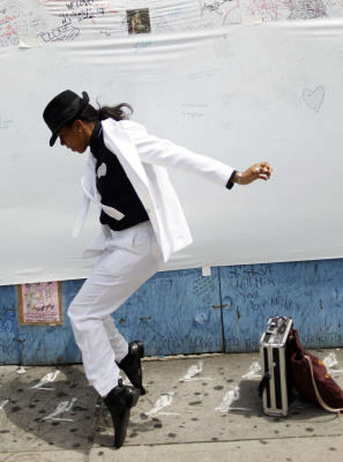 Moses Harper shows off her dance moves in front of banner in tribute to Michael Jackson in front of the Apollo Theatre in the Harlem neighborhood of New York today.