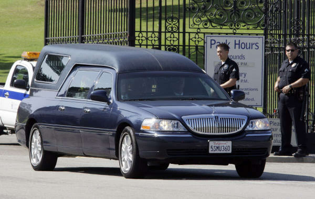 A hearse, part of a long convoy of cars, leaves Forest Lawn Memorial Park in Los Angeles Tuesday, July 7, 2009.