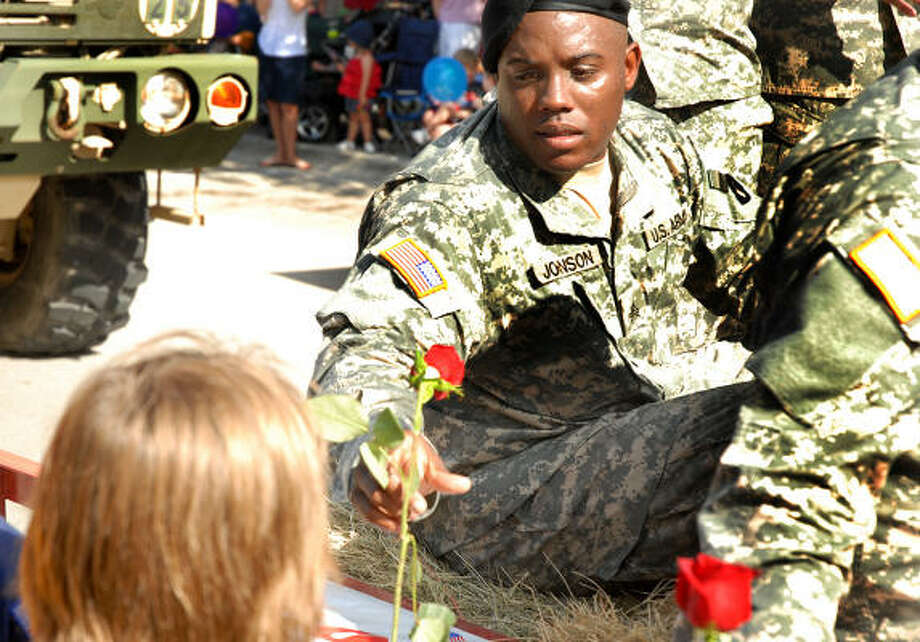 """WOODLANDS PARADE:Army Specialist Roneaka Johnson receives a rose from a Woodlands Cub Scout during the South Montgomery County Fourth of July Parade as it runs through Market Street. The theme of this year's parade was """"Traveling the U.S."""" and included floats, bands, local organizations and dignitaries. Photo: David Hopper, For The Chronicle"""