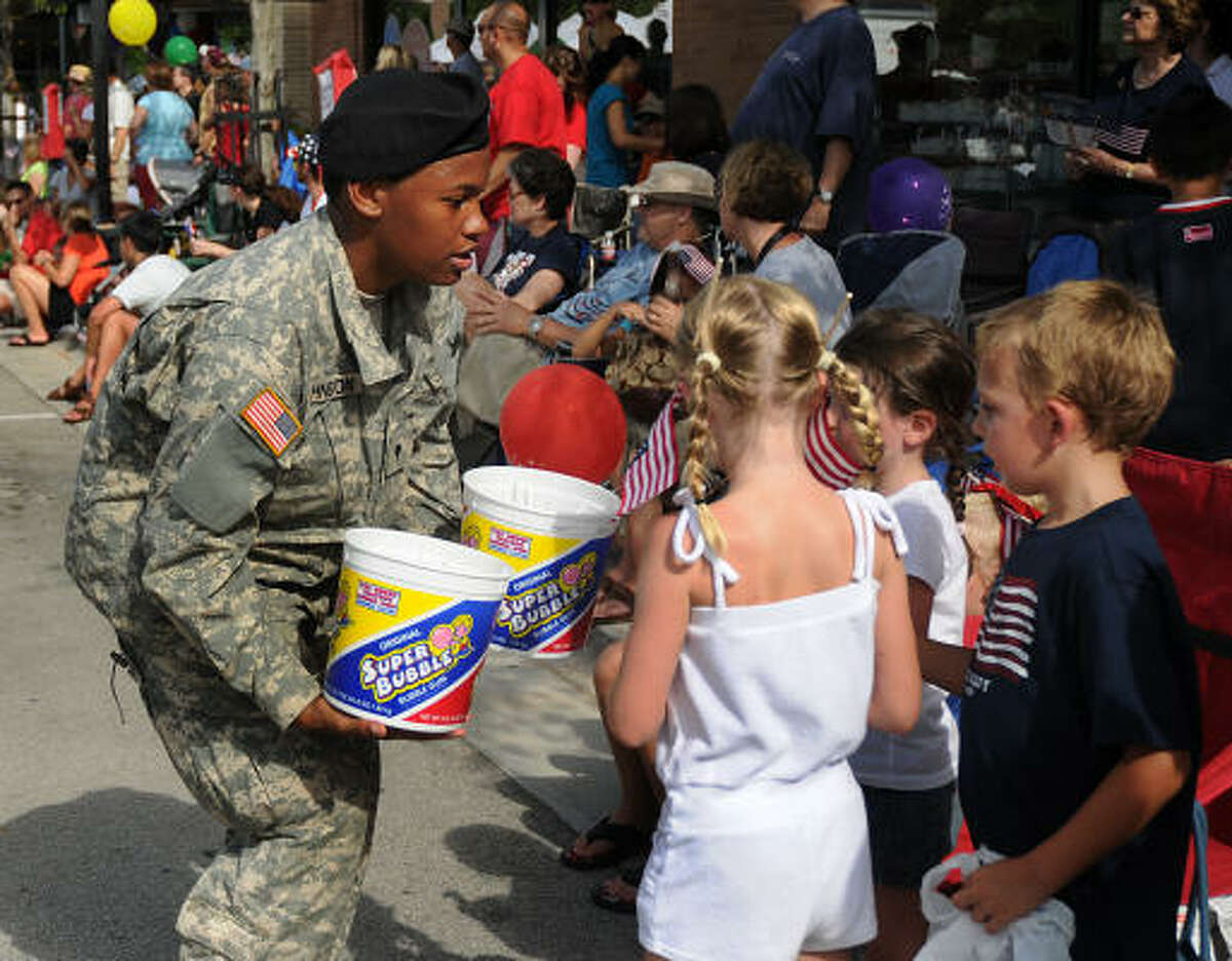 Army Specialist Roneaka Johnson hands out lollipops to spectators.
