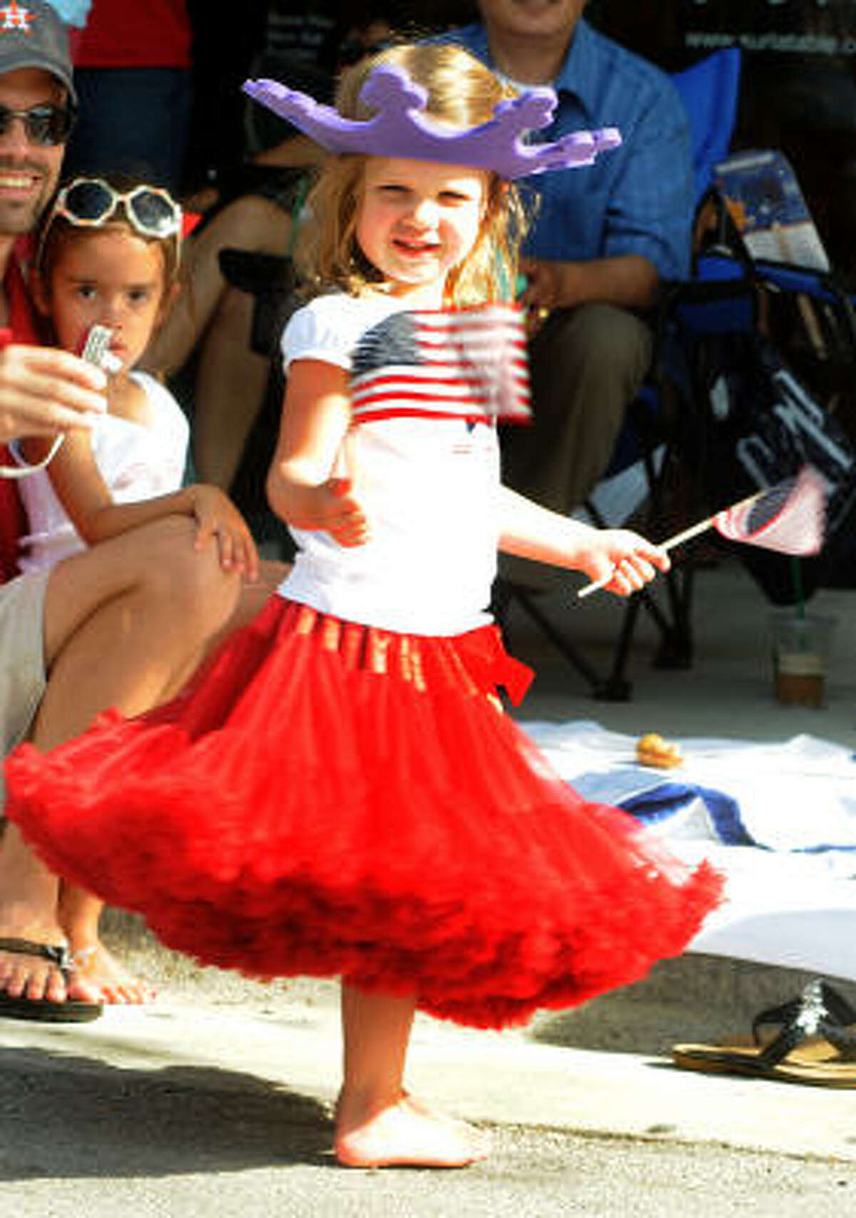 Three-year-old Isabelle Alman, of The Woodlands, waves her flags during the parade.