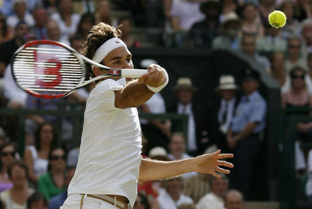 Roger Federer hits a forehand return to Andy Roddick on Sunday.