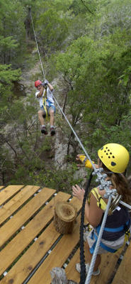 Mark Hogan of Austin traverses a zip line above the trees toward guide Bree Berwanger of Cypress Valley Canopy Tours, where visitors experience the Hill Country 40 to 55 feet from the ground. For more information on where to eat and stay, read the story here. Photo: Chronicle File