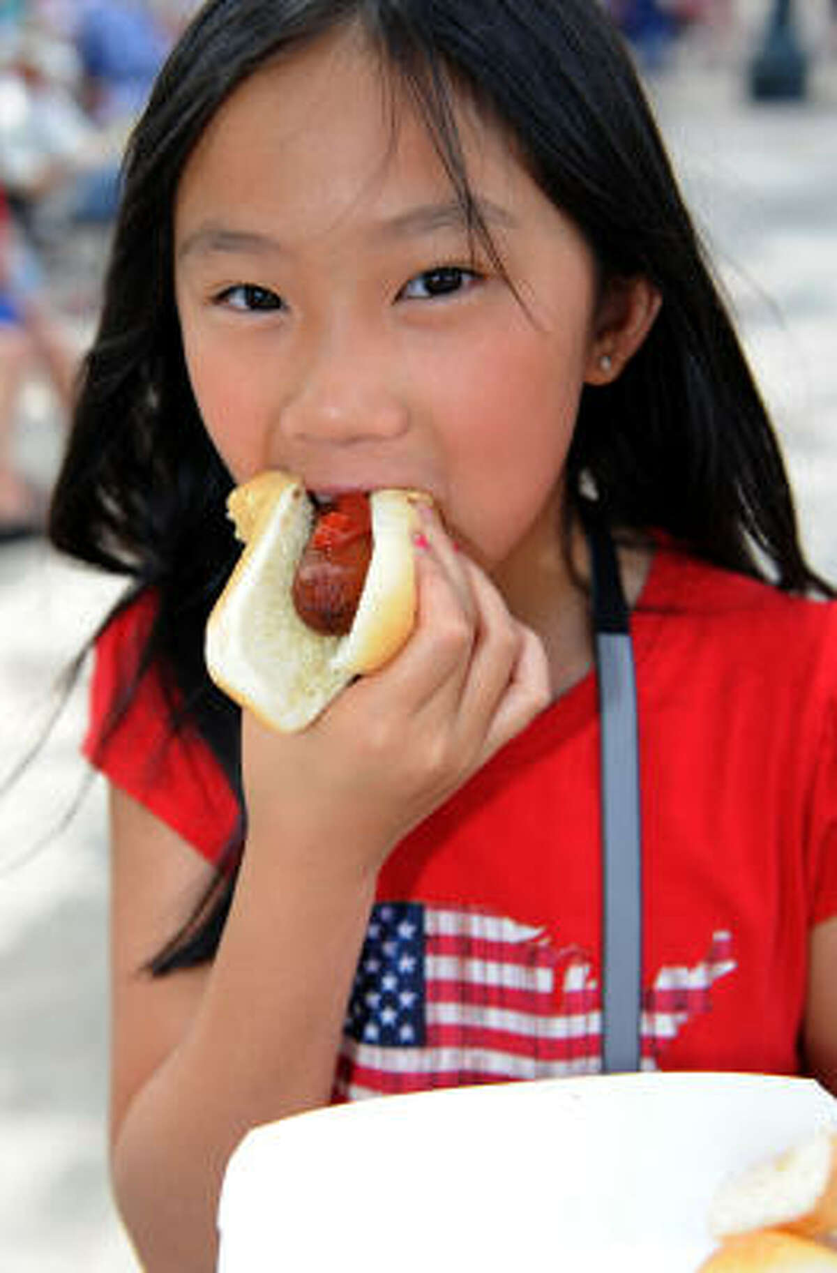 Alexis McNeilly, 10, enjoys a free hot dog at League Park.