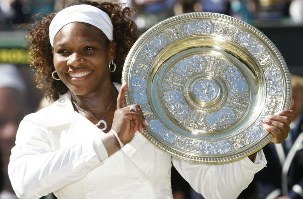 Serena Williams holds the championship trophy after winning her third Wimbledon title.
