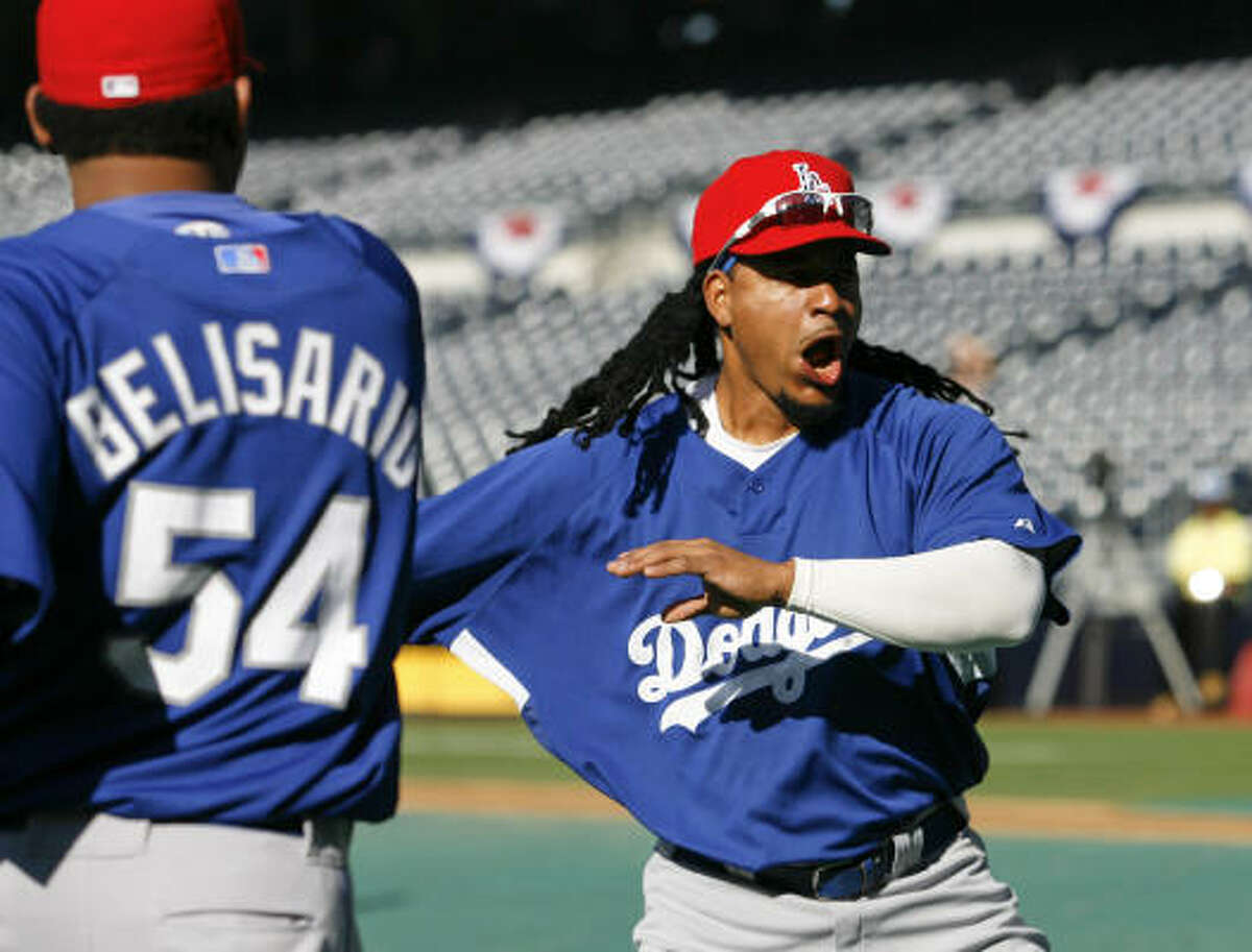 Dodgers left fielder Manny Ramirez stretches with teammate Ronald Belisario before Ramirez' return against the Padres on Friday.