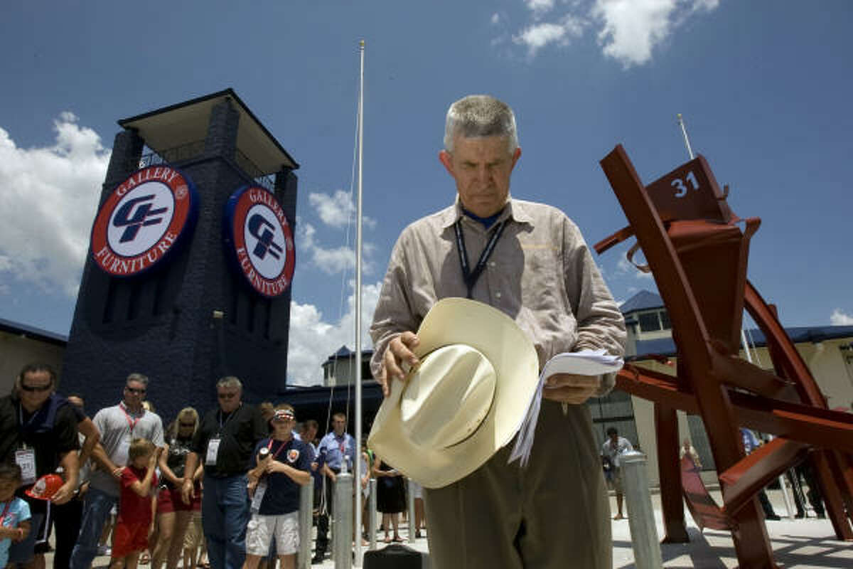 Standing before a sculpture honoring crews from 31 HFD stations that fought the fire, Jim McIngvale prays at the event.