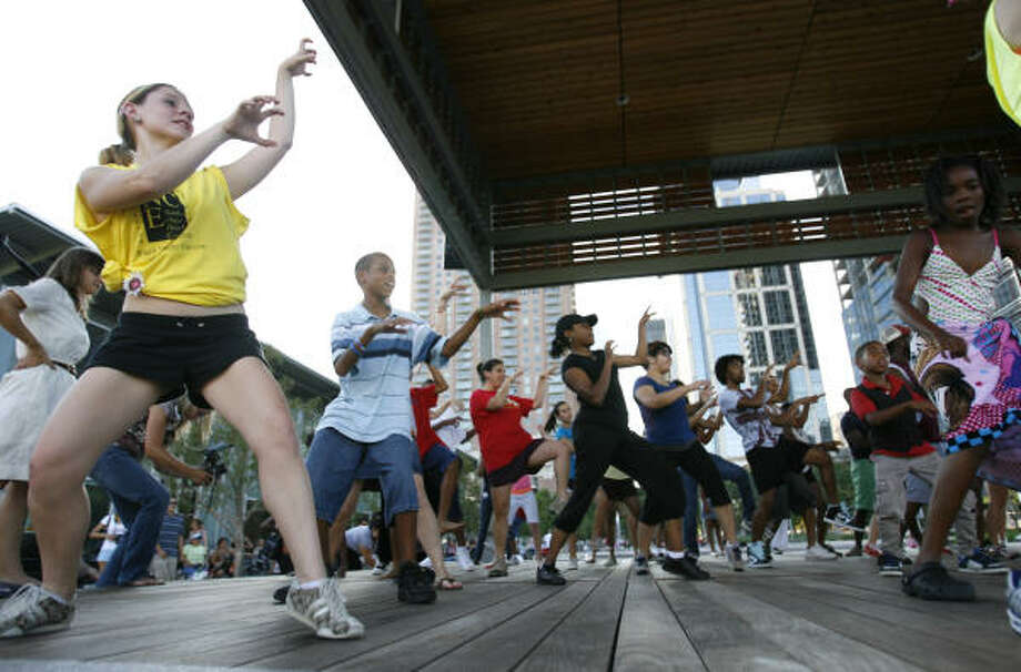 Cassandra Shaffer helps to lead the crowd dancing to the Michael Jackson song Thriller in Houston, as the Sandra Organ Dance Company teaches the crowd of more than 500, to dance on stage at the Discovery Green. Photo: Karen Warren, Chronicle
