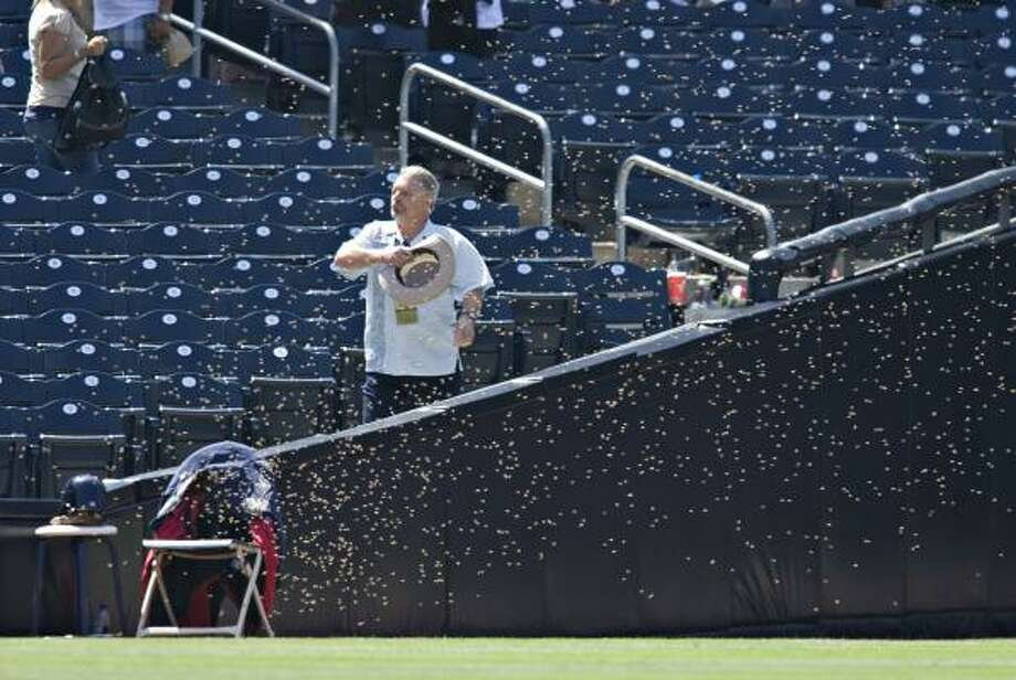 Astros 7, Padres 2An unidentified usher tries to move a swarm of bees as they cover a chair in left field during the ninth inning of Thursday's series finale. Photo: Denis Poroy, AP