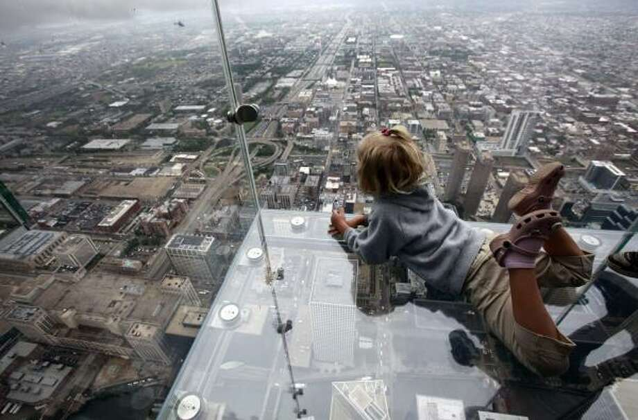 "Anna Kane, 5, of Alton, Ill., looks down from ""The Ledge,"" the new glass balconies suspended 1,353 feet in the air from the Sears Tower's 103rd floor Skydeck in Chicago. The Ledge opened to the public today. Photo: Kiichiro Sato, AP"