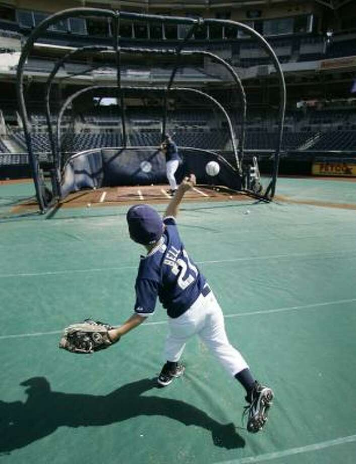 Reece Bell, the 5-year-old son of San Diego closer Heath Bell, throws batting practice to his father at Petco Park prior to the game against the Astros on Wednesday in San Diego. Photo: Lenny Ignelzi, AP