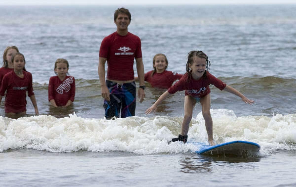Olivia Oldner, 5, of McKinney keeps her balance during the lesson from Bilabong/Ohana Surf and Skate Shop.
