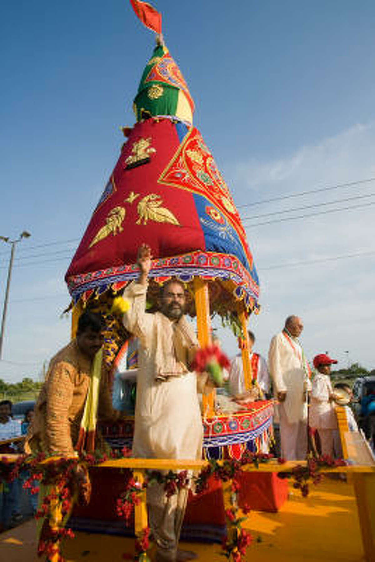 RATH YATRA: Priest Debanand Pati tosses flowers from the chariot at the Houston Rath Yatra festival (the Festival of Chariots) at the Shri Radha Krishna Temple on Beechnut.