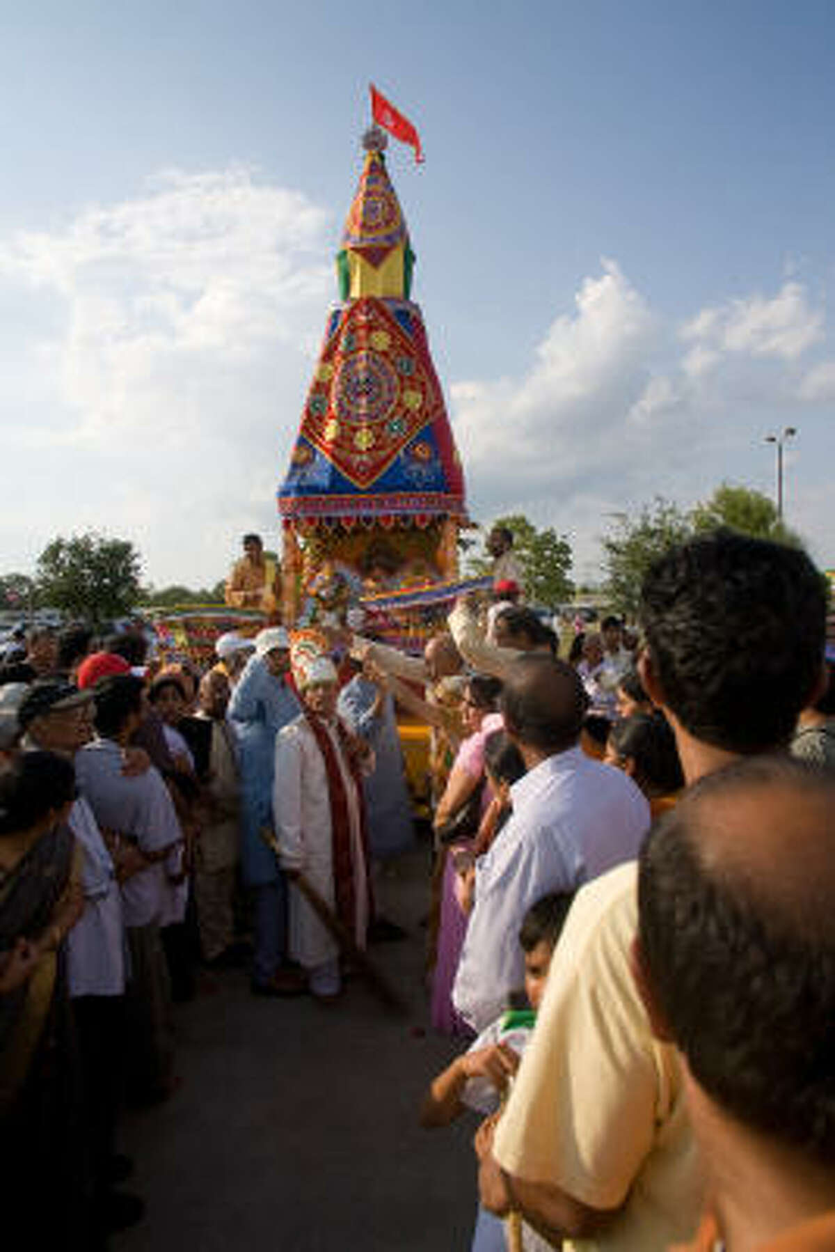 Devotees crowd around the chariot with the Deities.
